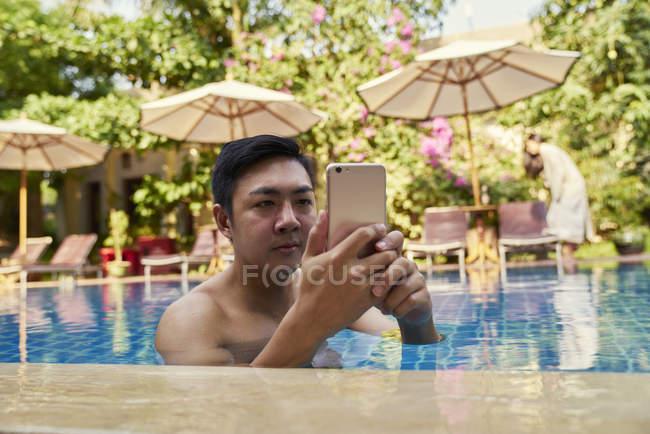 Jovem tirando fotos com seu celular na piscina — Fotografia de Stock