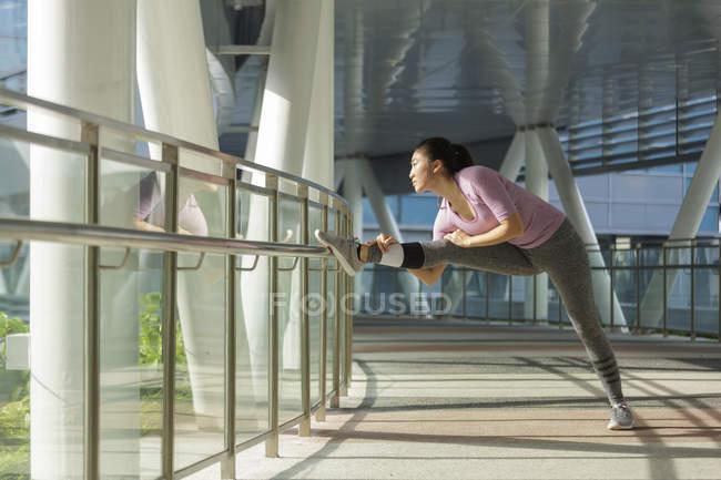 Une jeune femme asiatique s'étire avant son entraînement quotidien en cours d'exécution à Singapour — Photo de stock