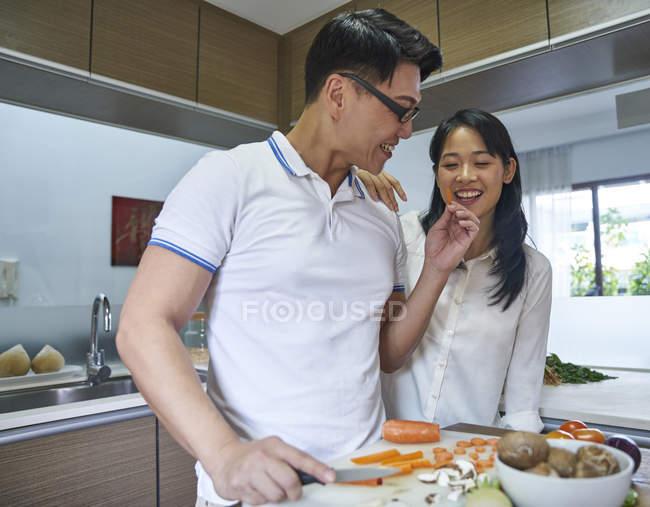 Счастливая азиатская пара готовит еду на кухне — стоковое фото