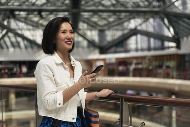 Joven casual asiático mujer usando inteligente en centro comercial - foto de stock