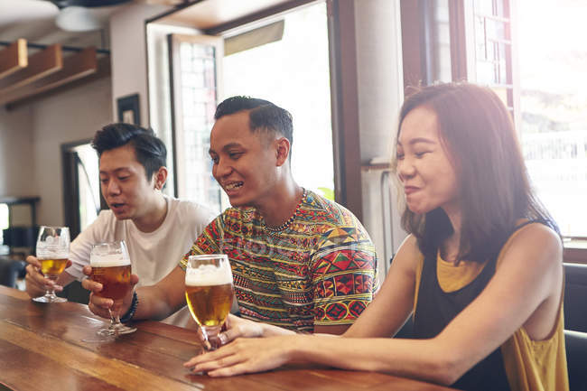 Young asian friends drinking beer together in bar — Stock Photo
