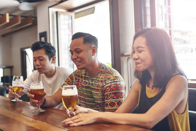 Jovens amigos asiáticos, bebendo cerveja juntos no bar — Fotografia de Stock