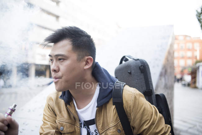 Young asian musician male with violin and vape in city — Stock Photo