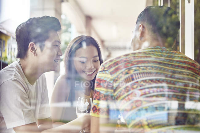 Young asian friends behind window together in bar — Stock Photo