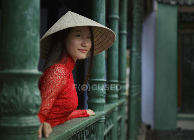 Vietnamese woman wearing conical hat standing on a balcony in Hoi An in her Ao Dai — Stock Photo
