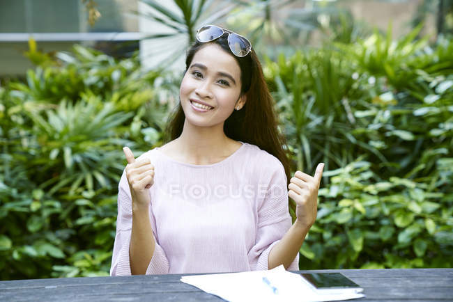 Happy young Malay lady on her laptop outdoors — Stock Photo