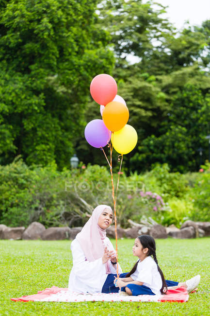 Mother and child with balloons in the park. — Stock Photo