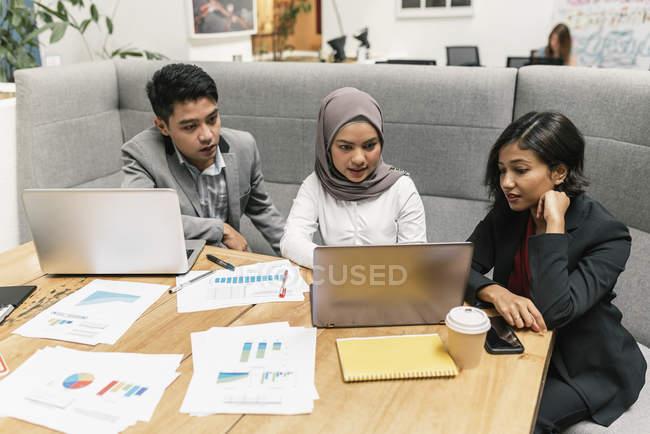Gente de negocios multicultural jóvenes trabajando con dispositivos digitales en la oficina moderna - foto de stock