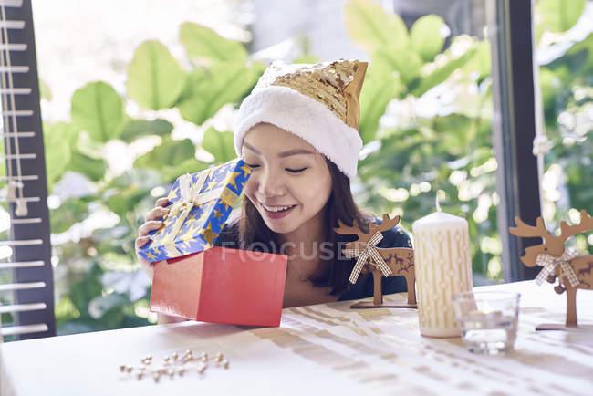 Щасливі азіатських брюнетки святкування Різдва і розпакування подарунок — стокове фото