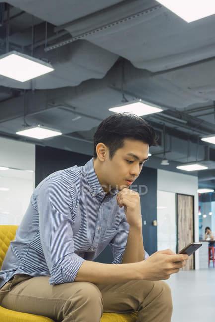 Молоді азіатські бізнесменом за допомогою смартфона в сучасні офісні — стокове фото