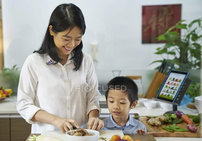 Happy young asian family cooking together at kitchen — Stock Photo