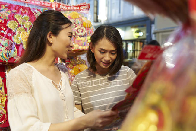 Young asian couple of friends spending time together on traditional bazaar at Chinese New Year — Stock Photo