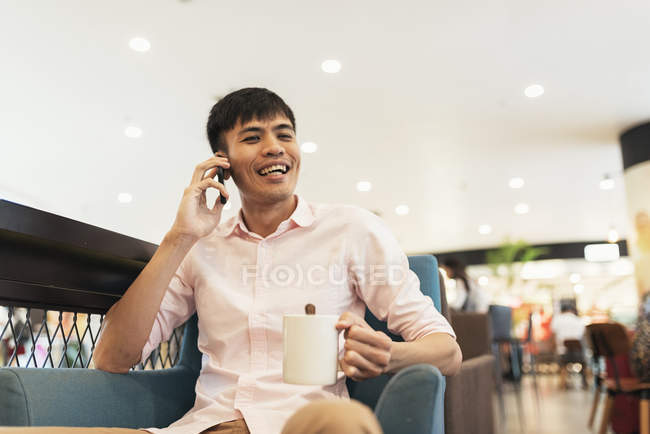 Attractive young asian man talking by smartphone and holding coffee — Stock Photo
