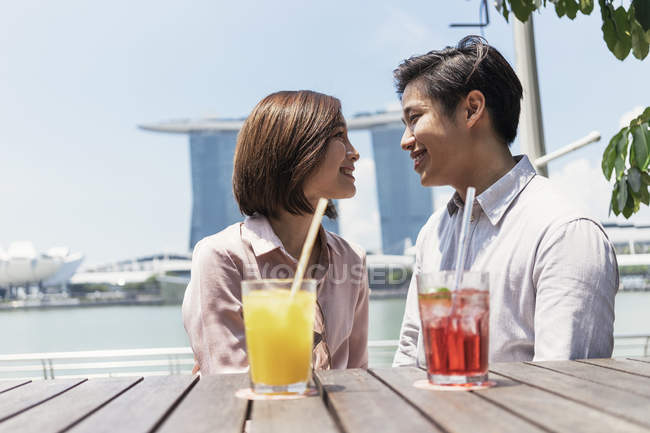 Young asian couple spending time together with drinks in Singapore — Stock Photo