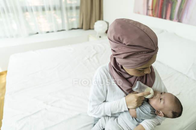 Asiatico musulmana madre alimentazione il suo bambino a casa — Foto stock