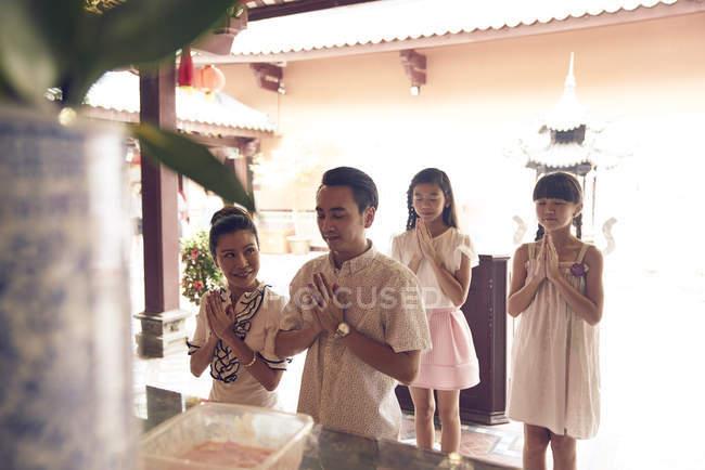 Young happy asian family praying shrine — Stock Photo