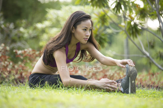 A young asian woman is doing yoga in the park at Marina Bay. — Stock Photo