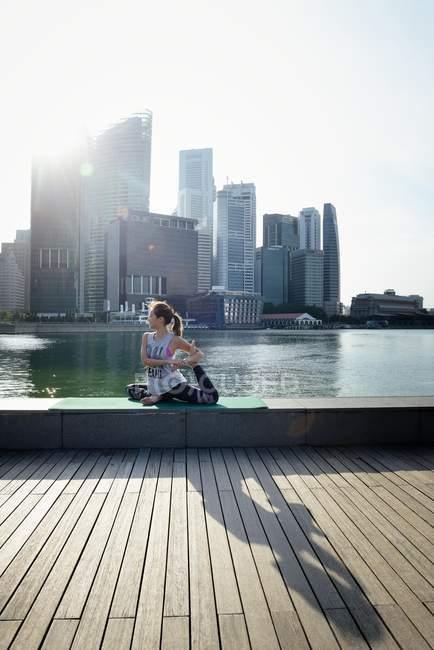 Giovane donna asiatica sportiva fare yoga contro quartiere degli affari — Foto stock
