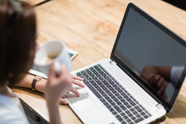 Young woman seated in front of her laptop, having a cup of coffee. — Stock Photo
