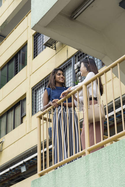Young casual asian girls standing on balcony — Stock Photo