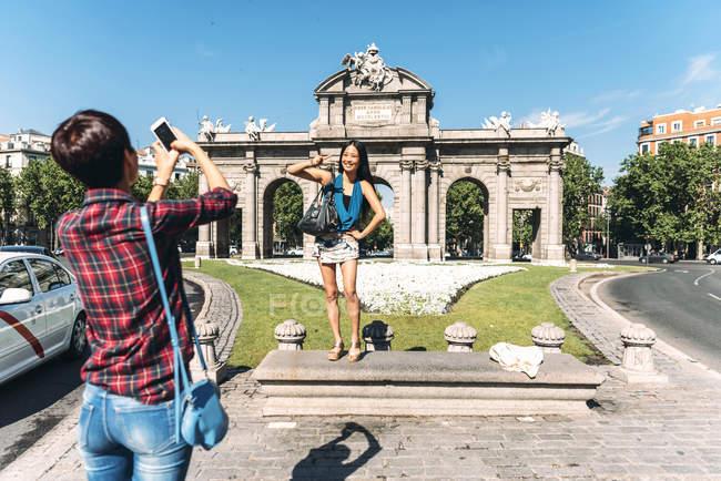 Turista cinese che scatta foto di un'amica giapponese sullo sfondo della Puerta de Alcala (Porta Alcala) a Madrid, Spagna . — Foto stock