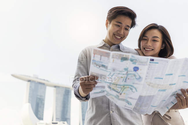 Young asian couple sharing map together — Stock Photo