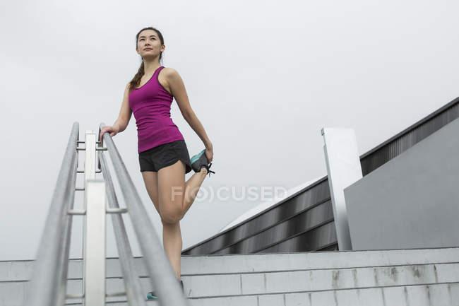 Une jeune femme asiatique est qui s'étend sur un escalier extérieur avant sa course — Photo de stock
