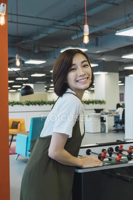 Молодых азиатских бизнес женщина играет в футбол в современном офисе — стоковое фото