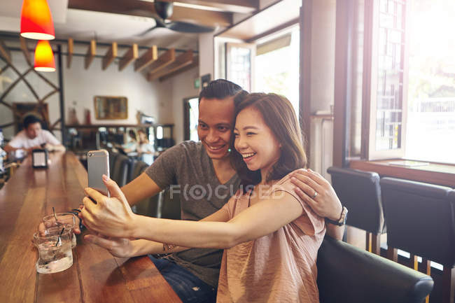 Young asian friends taking selfie together in bar — Stock Photo