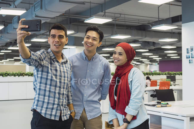 Jóvenes asiático negocios personas tomando selfie en moderno oficina - foto de stock