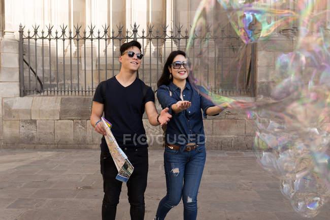 Schöne junge asiatische paar Urlaub in Barcelona verbringen und Blick auf den großen Seifenblasen — Stockfoto
