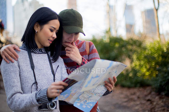 Heureux couple de touristes tenant la carte dans le parc central — Photo de stock