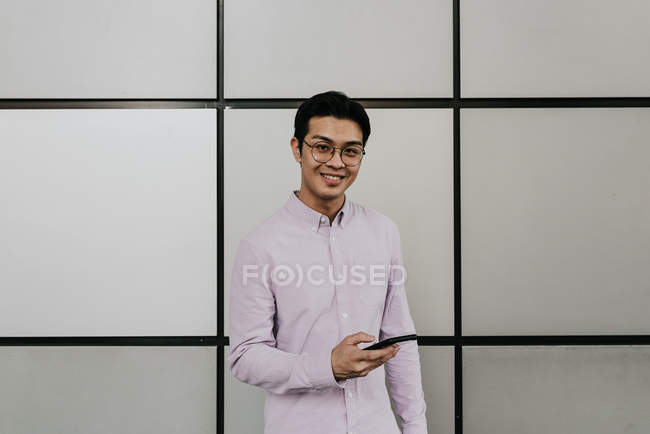 Young casual asian man using smartphone — Stock Photo