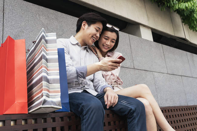 Young asian couple spending time together with smartphone — Stock Photo