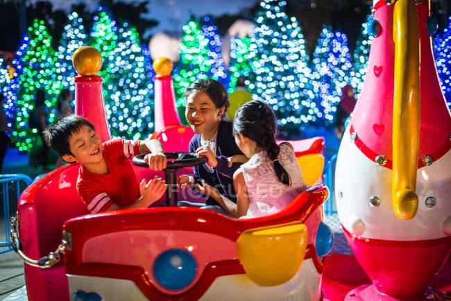 Happy asian siblings spending time together in amusement park at christmas — Stock Photo