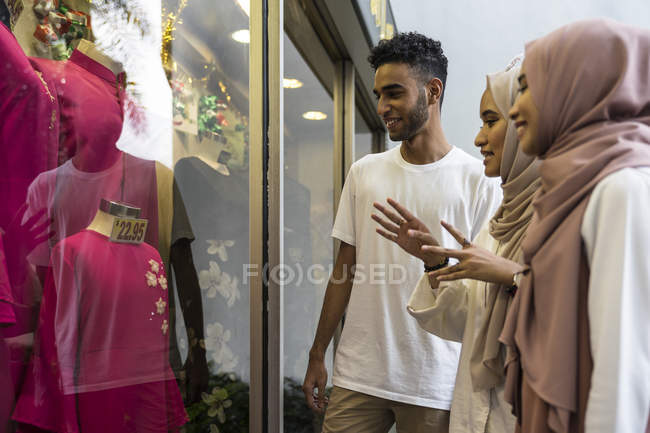 Group of happy muslim friends shopping and looking at shop window — Stock Photo