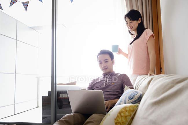 Зрелая азиатская случайная пара, использующая ноутбук вместе — стоковое фото