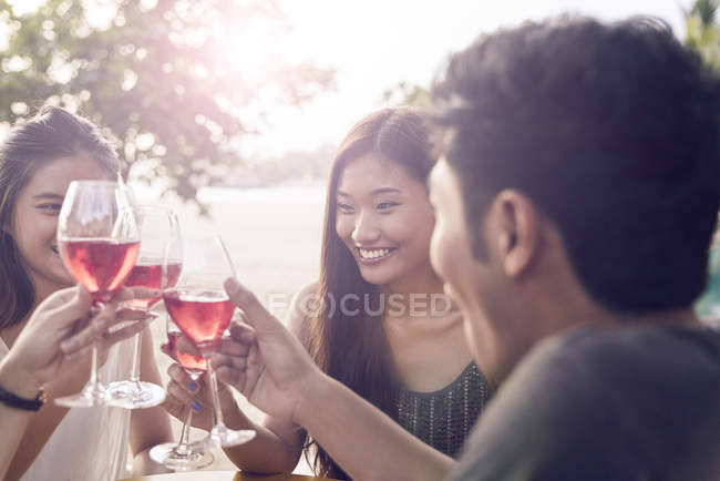 Attractive young asian friends having drink — Stock Photo