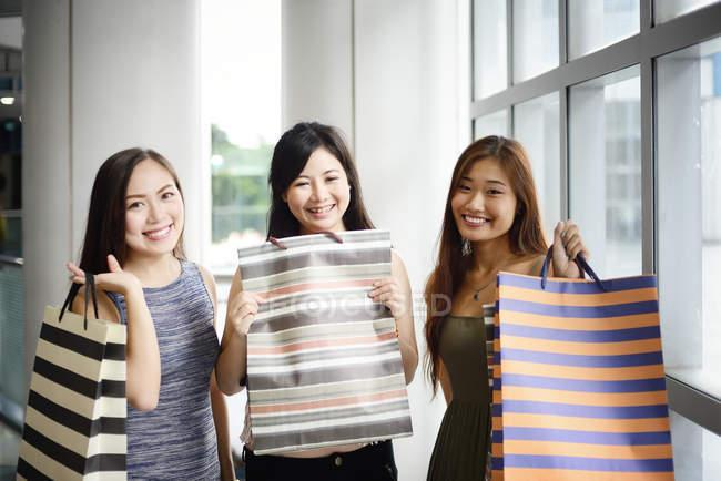 Lindo asiático mujeres con compras bolsas - foto de stock