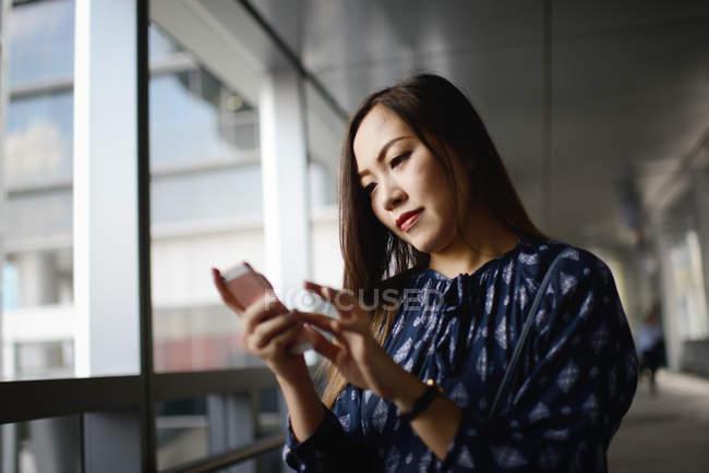 Щасливі красиві азіатські жінки за допомогою смартфона — стокове фото