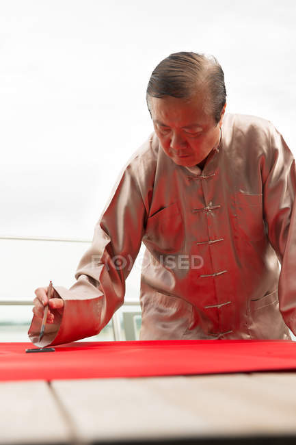 Old asian man drawing calligraphy hieroglyphs at chinese new year — Stock Photo