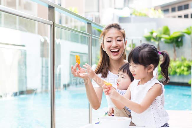 Kinder genießen gemeinsam mit Mutter Snack. — Stockfoto