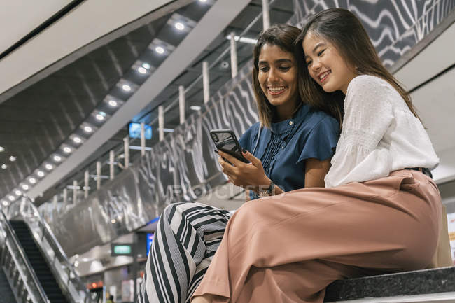 Young casual asian girls using smartphone together — Stock Photo