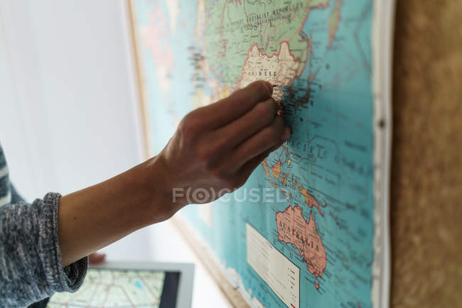 Cropped image of man pinning the world map — Stock Photo