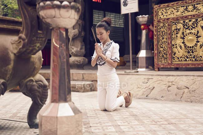 Mujer asiática joven orando en el templo del Buda de - foto de stock