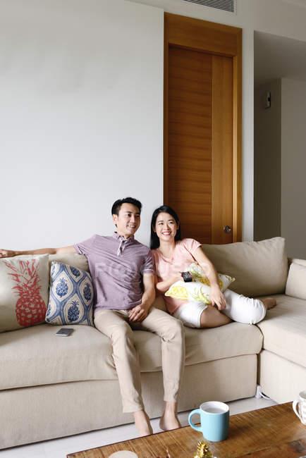 Літня азіатських випадковий пара, сидячи на дивані у себе вдома і дивитися телевізор — стокове фото