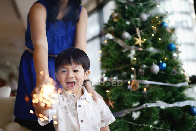 Asian family celebrating Christmas holiday with firework sparkler — Stock Photo