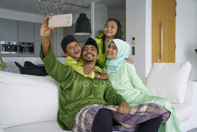 Young asian family celebrating Hari Raya together at home and taking selfie — Stock Photo
