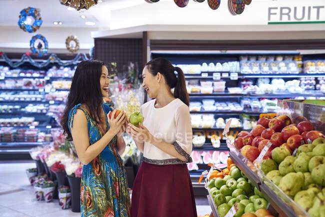 Dois jovens asiáticos mulheres compras juntos no shopping para comida — Fotografia de Stock
