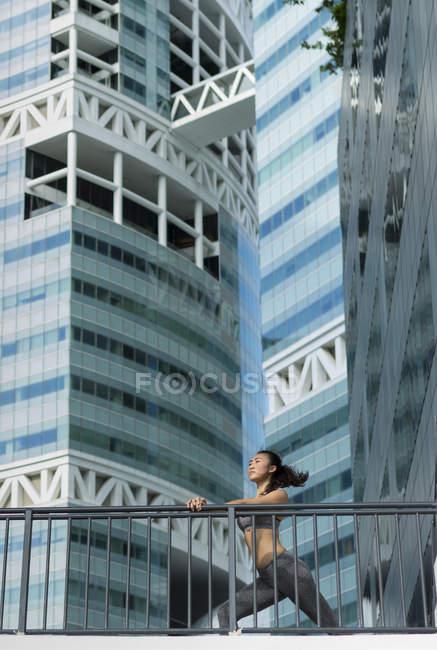 Une jeune femme asiatique s'étire avant son entraînement quotidien en cours d'exécution dans la ville de favori — Photo de stock